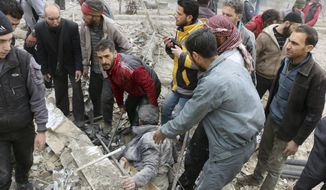 This photo provided by the Syrian Civil Defense group known as the White Helmets, shows men pulling a survivor from the rubble after airstrikes hit a rebel-held suburb near Damascus, Syria, Monday, Feb. 5, 2018. Syrian opposition activists said more than one dozen people killed in new airstrikes. (Syrian Civil Defense White Helmets via AP)