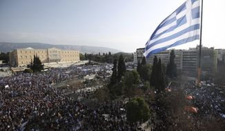 A giant Greek flag hangs from a crane waves over protesters during a rally in Athens, Sunday, Feb. 4, 2018. Protesters from across Greece were thronging the Greek capital's main square outside parliament Sunday to protest a potential Greek compromise in a dispute with neighboring Macedonia over the former Yugoslav republic's official name. (AP Photo/Thanassis Stavrakis)