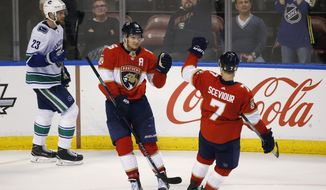 Florida Panthers center Aleksander Barkov, center, is congratulated by center Colton Sceviour (7) after Barkov scored during the third period of an NHL hockey game against the Vancouver Canucks, Tuesday, Feb. 6, 2018, in Sunrise, Fla. The Panthers defeated the Canucks 3-1. (AP Photo/Wilfredo Lee)