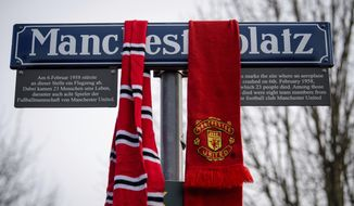 Scarfs of soccer fans hang on the Manchesterplatz street sign during a commemoration ceremony on the Manchester place at the Munich Riem airport, southern Germany, Tuesday, Feb. 6, 2018. Sixty years ago on Feb. 6, 1958 a plane with professional players of the Manchester United soccer club on board crashed in Munich with 21 survivors and 23 fatalities. (Matthias Balk/dpa via AP)