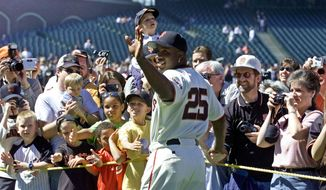 FILE - In this April 13, 2002, file photo, San Francisco Giants' Barry Bonds waves and poses for fans during the annual on-field photo day before the Giants' baseball game against the Milwaukee Brewers in San Francisco. Bonds will have his No. 25 jersey retired this August by the Giants when his former Pittsburgh Pirates are in town, the team announced Tuesday, Feb. 6, 2018. (AP Photo/Eric Risberg, File)
