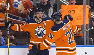 Edmonton Oilers' Connor McDavid (97) and Leon Draisaitl (29) celebrate a goal against the Tampa Bay Lightning during second period NHL hockey action in Edmonton, Alberta, Monday, Feb. 5, 2018. (Jason Franson/The Canadian Press via AP)