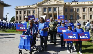 A coalition of groups march during a rally to build support for extending the life of the Navajo Generating Station power plant near the Arizona-Utah border, in front of the Arizona Capitol Tuesday, Feb. 6, 2018, in Phoenix. (AP Photo/Ross D. Franklin)