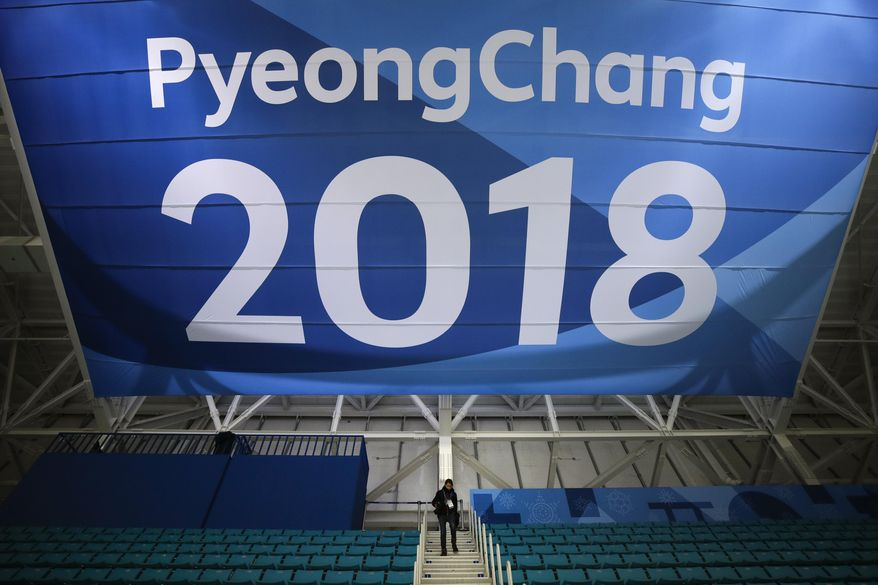 FILE - In this Feb. 6, 2018 file photo, a photographer walks down the steps underneath a large banner at the Gangneung Hockey Center ahead of the 2018 Winter Olympics in Gangneung, South Korea. Fresh off the Super Bowl, NBC begins more than two weeks of Winter Olympics coverage on Thursday, Feb. 8,  with a new host, some new wrinkles and the hope that its business model keeps pace with the different ways people experience events on television and online. (AP Photo/Jae C. Hong, File)