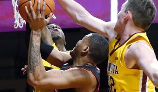 Minnesota's Michael Hurt, right, blocks a shot attempt by Nebraska's James Palmer Jr. in the first half of an NCAA college basketball game Tuesday, Feb. 6, 2018, in Minneapolis. (AP Photo/Jim Mone)