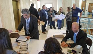 Former Rep. Rick Miera of Albuquerque left foreground, and Rep. Bill McCamley of Mesilla Park, right, file declarations of candidacy to run for statewide office at the New Mexico Secretary of State's Office in Santa Fe, N.M., on Tuesday, Feb. 6, 2018. Miera is running for lieutenant governor and McCamley is running for state auditor. The deadline arrived Tuesday for major party candidates in New Mexico to turn in nominating petitions in order to run for statewide or federal office. (AP Photo/Morgan Lee)