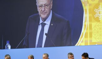 International Olympic Committee member and Court of Arbitration for Sport president John Coates is projected on a screen as he delivers a report on the Tokyo 2020 Summer Olympics during the 132nd IOC Session prior to the 2018 Winter Olympics in Pyeongchang, South Korea, Wednesday, Feb. 7, 2018. Pictured below Coates are Ugur Erdener of Turkey, from bottom left, Zaiqing Yu of China, former IOC President Jacques Rogge, IOC President Thomas Bach and Christophe De Kepper of Belgium. (AP Photo/Patrick Semansky)