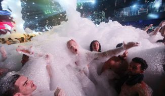 FILE - In this March 16, 2015, file photo, partygoers dance in foam at The City nightclub in the Caribbean resort city of Cancun, Mexico. While beach destinations remain popular for spring break, travel agents say customers are also demanding unique cultural experiences and active outdoorsy adventures. (AP Photo/Israel Leal, File)