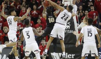 Cincinnati's Kyle Washington (24) blocks a shot by Central Florida's Dayon Griffin (10) in the first half of an NCAA college basketball game, Tuesday, Feb. 6, 2018, in Highland Heights, Ky. (AP Photo/John Minchillo)