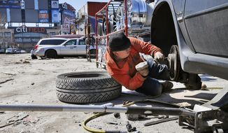 FILE - In this April 2, 2015 photo, CitiField, home to the New York Mets, is visible from a dusty, unpaved street in the Willets Point section of Queens, New York, where Jorge works on repairing a car. A long-planned redevelopment project for the neighborhood is back on the drawing board. The new plan is for three, 100 percent affordable buildings including a standalone building with 220 homes for low-income seniors and apartments for families at lower incomes than originally proposed. The plan also includes public open space and a new 450-seat public elementary school, according to a statement from Mayor Bill de Blasio's office. (AP Photo/Kathy Willens, File)