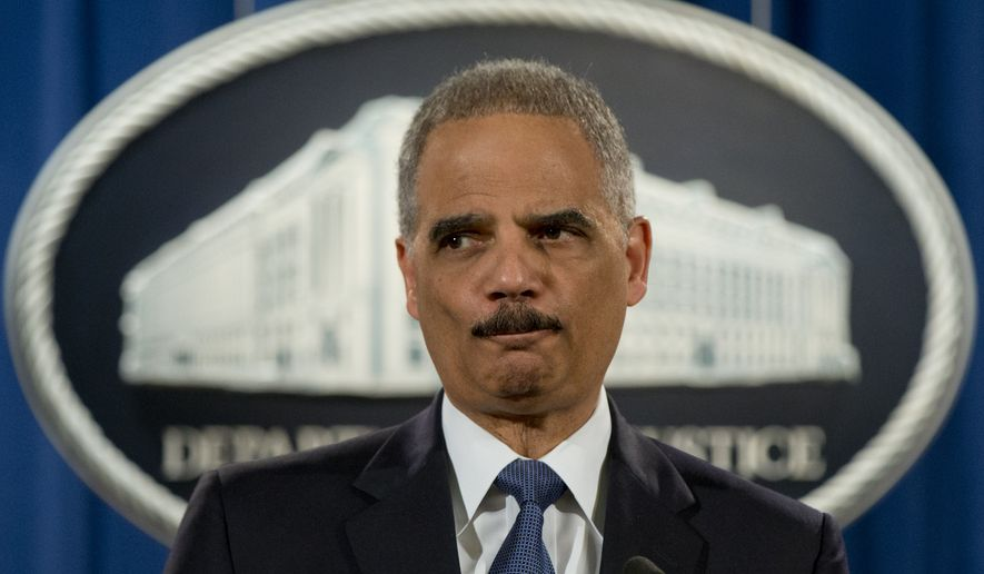 Then-Attorney General Eric Holder pauses as he speaks at the Justice Department in Washington to discuss the Aug. 9, 2014, shooting in Ferguson, Mo., on March 4, 2015. (Associated Press) **FILE**