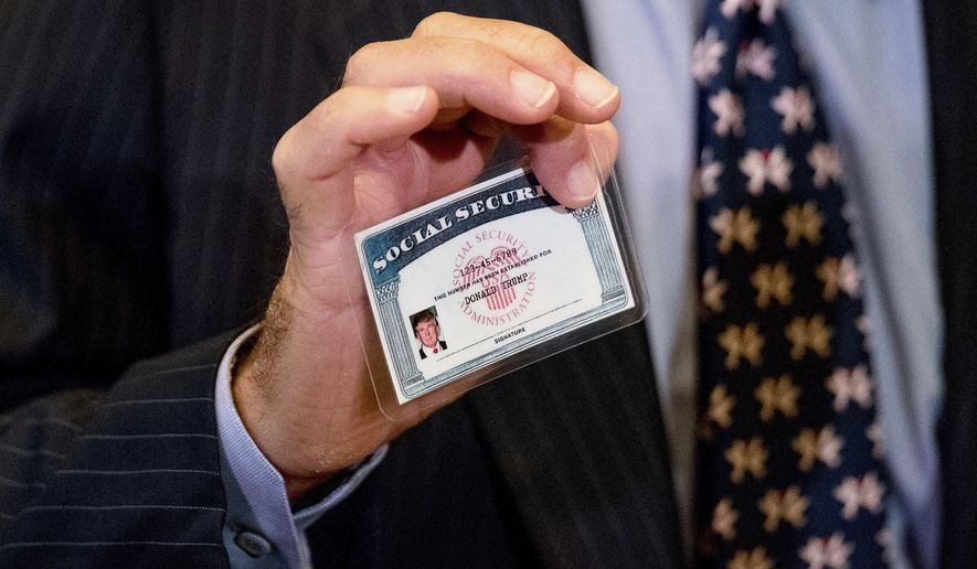 William Wachtel holds up a mock Social Security card of President-elect Donald Trump as he speaks to members of the media following a meeting with Trump at Trump Tower in New York, Monday, Jan. 16, 2017. (AP Photo/Andrew Harnik)