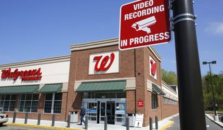 In this Wednesday, May 14, 2014 photo a passer-by walks near the entrance of Walgreens store in Boston, where a sign advises video surveillance recording is in progress for security. (AP Photo/Steven Senne)