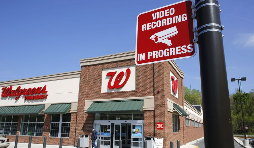 In this Wednesday, May 14, 2014, file photo a passer-by walks near the entrance of Walgreens store in Boston, where a sign advises video surveillance recording is in progress for security. (AP Photo/Steven Senne)  ** FILE **