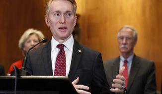 Sen. James Lankford, R-Okla., left, with Sen. Angus King, I-Maine, right, speaks about immigration and the Deferred Action for Childhood Arrivals (DACA) program Wednesday, Feb. 7, 2018, on Capitol Hill in Washington. (AP Photo/Jacquelyn Martin) **FILE**