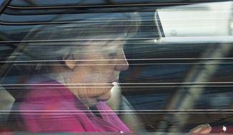 German Chancellor Angela Merkel leaves in a car after coalition talks in the headquarters of the Christian Democratic Union in Berlin Germany, Wednesday, Feb. 7, 2018. German news agency dpa is reporting that Merkel's conservatives and Germany's main center-left party have reached an agreement to form a new coalition government after a final session of negotiations that dragged on for 24 hours. (Bernd von Jutrczenka/dpa via AP)