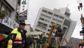 A police officer guards outside of a collapsed apartment building in Hualien County, eastern Taiwan, Wednesday, Feb. 7, 2018. A strong earthquake struck eastern Taiwan late Tuesday night. (AP Photo/Chiang Ying-ying)