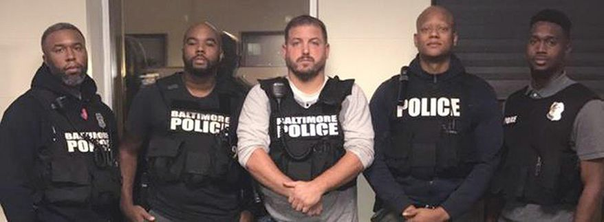 In this October 2016 photo released by the Baltimore police, officers, Det. Evodio Hendrix, Det. Marcus Taylor, Sgt. Wayne Jenkins, Det. Jemell Rayam, Det. Maurice Ward, from left, are seen in Baltimore. Federal prosecutors and defense attorneys are set to make their closing arguments Wednesday, Feb. 7, 2018, in the trial of two Baltimore detectives, Marcus Taylor and Daniel Hersl, fighting racketeering and robbery charges. The case involves one of the worst U.S. police corruption scandals in recent memory. (Baltimore Police Department/The Baltimore Sun via AP)