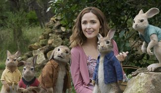 """This image released by Columbia Pictures shows Rose Byrne with characters, from left, Mopsy, voiced by Elizabeth Debicki, Flopsy, voiced by Margot Robbie, Benjamin, voiced by Colin Moody, Peter Rabbit, voiced by James Corden and Cottontail, voiced by Daisy Ridley in a scene from """"Peter Rabbit."""" (Columbia Pictures/Sony via AP)"""