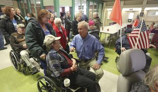 FILE - In this Jan. 10, 2018 file photo, Gov. Bruce Rauner, center, talks with members of the Illinois Veterans Home after staying at the home in Quincy, Ill., to better understand the operations there, after it experienced a deadly Legionnaires' disease outbreak. Rauner's administration is requiring state lawmakers to jump through a public-records law hoop before turning over emails about the outbreak at the Veterans Home. Illinois Public Health Director Dr. Nirav Shah said Wednesday Feb. 7, 2018that Sen. Tom Cullerton's request for communication surrounding the crisis is subject to the Freedom of Information Act. (Phil Carlson/The Quincy Herald-Whig via AP File)