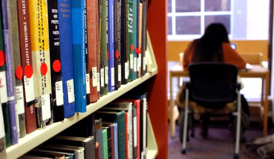 In a Jan. 25, 2018, photo, Dierra Rowland, 19, of Philadelphia, studies at the Indiana University of Pennsylvania library in Indiana, Pa., near a shelf of books marked with red stickers, meaning they might be removed from the shelves. IUP is planning to remove tens of thousands of books that have little or no readership. (AP Photo/Michael Rubinkam)