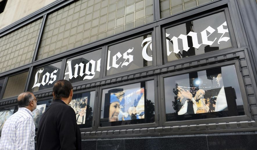 FILE - In this May 16, 2016, file photo, pedestrians look at news photos posted outside the Los Angeles Times building in downtown Los Angeles. It was announced Wednesday, Feb. 7, 2018, that the Los Angeles Times is being sold to Dr. Patrick Soon-Shiong, a local billionaire, for $500 million, ending its strained tenure under the owner of the Chicago Tribune. Soon-Shiong is a major shareholder of Chicago's Tronc Inc., one of the richest men in Los Angeles and, according to Forbes, the nation's wealthiest doctor, with a net worth of $7.8 billion. (AP Photo/Richard Vogel, File)
