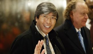 In this Jan. 10, 2017, file photo, pharmaceuticals billionaire Dr. Patrick Soon-Shiong waves as he arrives in the lobby of Trump Tower in New York for a meeting with President-elect Donald Trump. It was announced Wednesday, Feb. 7, 2018, that the Los Angeles Times is being sold to Soon-Shiong, a local billionaire, for $500 million, ending its strained tenure under the owner of the Chicago Tribune. (AP Photo/Evan Vucci, File)