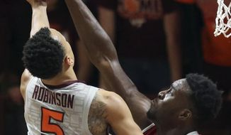 Virginia Tech's Justin Robinson (5) is fouled by North Carolina State's Abdul-Malik Abu (0) during the first half of an NCAA college basketball game in Blacksburg, Va., Wednesday, Feb. 7, 2018. (Matt Gentry/The Roanoke Times via AP)