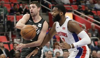 Brooklyn Nets guard Joe Harris passes the ball as Detroit Pistons center Andre Drummond (0) closes in during the first half of an NBA basketball game Wednesday, Feb. 7, 2018, in Detroit. (AP Photo/Carlos Osorio)