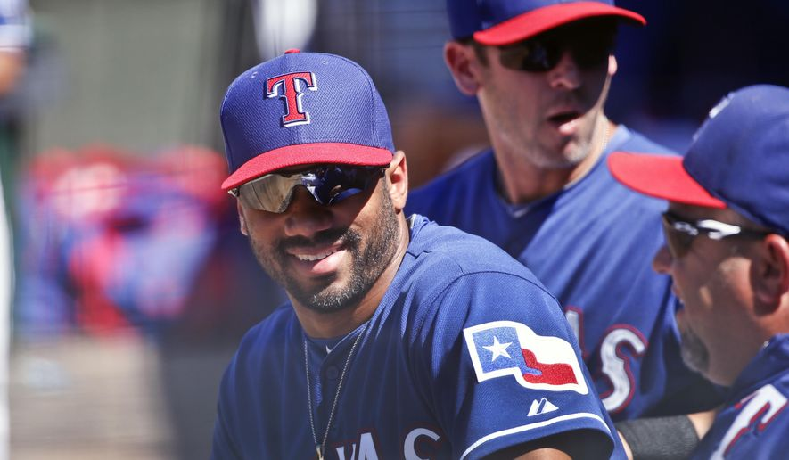 FILE - This March 28, 2015 file photo shows Seattle Seahawks quarterback Russell Wilson talking with fellow Texas Rangers in the dugout during a spring training baseball game between the Texas Rangers and the San Diego Padres in Surprise, Ariz. Wilson has been traded from the Texas Rangers to the New York Yankees. The Rangers selected Wilson in the Triple-A portion of the Rule 5 draft during the winter meetings in December 2013, about two months before he led the Seahawks to a win over Denver in the Super Bowl. (AP Photo/Lenny Ignelzi)