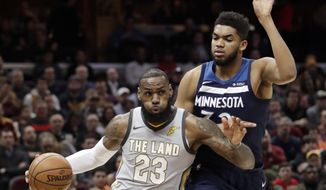 Cleveland Cavaliers' LeBron James, left, drives against Minnesota Timberwolves' Karl-Anthony Towns in the first half of an NBA basketball game, Wednesday, Feb. 7, 2018, in Cleveland. (AP Photo/Tony Dejak)