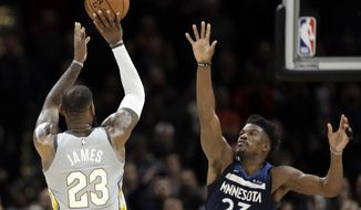 Cleveland Cavaliers' LeBron James, left, shoots over Minnesota Timberwolves' Jimmy Butler for the game-winning basket in overtime of an NBA basketball game, Wednesday, Feb. 7, 2018, in Cleveland. The Cavaliers won 140-138 in overtime. (AP Photo/Tony Dejak)