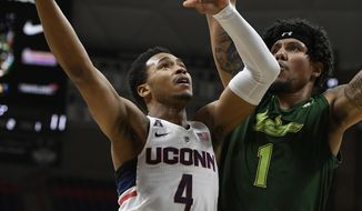 Connecticut's Jalen Adams, left, goes up for a basket as South Florida's Isaiah Manderson, right, defends during the first half an NCAA college basketball game, Wednesday, Feb. 7, 2018, in Storrs, Conn. (AP Photo/Jessica Hill)
