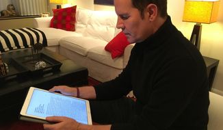 Juan Carlos Cruz reads from his tablet during an interview with The Associated Press in Philadelphia, Sunday Feb. 4, 2017. Cruz says Pope Francis received a letter he wrote in 2015 detailing the sexual abuse he suffered at the hands of a priest and efforts by the Chilean church to cover it up, contradicting the pope's recent insistence that no victims had come forward. (AP Photo/Yvonne Lee)