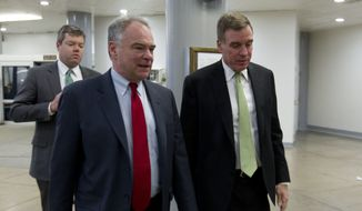 Sen. Tim Kaine, D-Va., speaks with Sen. Mark Warner, D-Va., as they walk to the Senate floor, Thursday, Feb. 8, 2018, at Capitol Hill in Washington. (AP Photo/Jose Luis Magana)
