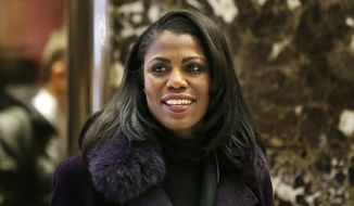 Omarosa Manigault smiles at reporters as she walks through the lobby of Trump Tower in New York, Dec. 13, 2016. (AP Photo/Seth Wenig) ** FILE **
