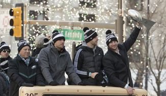 Philadelphia Eagles Carson Wentz, right, holds up the Vince Lombardi trophy as he rides with Nate Sudfeld, center right, Nick Foles, center left, and owner Jeffrey Lurie, left, during a Super Bowl victory parade, Thursday, Feb. 8, 2018, in Philadelphia. The Eagles beat the New England Patriots 41-33 in Super Bowl 52. (AP Photo/Christopher Szagola) **FILE**