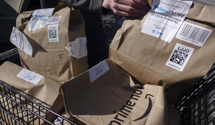 Amazon Prime Now bags full of groceries are loaded for delivery by a part-time worker outside a Whole Foods store, Thursday, Feb. 8, 2018, in Cincinnati. (AP Photo/John Minchillo) ** FILE **