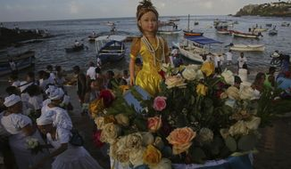 In this Feb. 2, 2018 photo, a large doll representing sea goddess Yemanja is taken to the sea from Red River Beach in Salvador, Brazil. Thousands of Brazilians have flooded the city's beaches in the northeast to pay tribute to the sea goddess and ask for her protection ahead of Carnival celebrations. (AP Photo/Eraldo Peres)