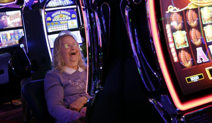 """Helen Solcberg plays a video slot machine at the public opening of Resorts World Catskills in Monticello, N.Y., Thursday, Feb. 8, 2018.  The casino is opening Thursday in the heart of the old """"Borscht Belt."""" It will feature more than 150 table games and 2,150 slot machines about 80 miles northwest of New York City. Promoted as economic boost to this old resort area, it is opening in an increasingly competitive regional market.  (AP Photo/Seth Wenig)"""