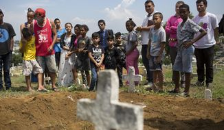 Friends and family surround the gravesite of 13-year-old Jeremias Moraes da Silva, during a burial ceremony at a cemetery, in Rio de Janeiro, Brazil, Thursday, Feb. 8, 2018. Jeremias was walking home after playing soccer Tuesday, when he was struck by a stray bullet during a police operation in the Mare slum. He died shortly after being rushed to the hospital. (AP Photo/Silvia Izquierdo)