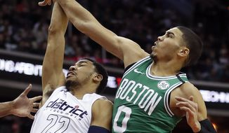 Washington Wizards forward Otto Porter Jr. (22) is fouled by Boston Celtics forward Jayson Tatum (0) during the first half of an NBA basketball game Thursday, Feb. 8, 2018, in Washington. (AP Photo/Pablo Martinez Monsivais)