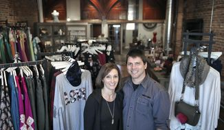 In this Friday, Feb. 2, 2018 photo, Kari and Shawn Reents stand inside their renovated women's clothing store, Velvet and Tulle Boutique, 217 W. Milwaukee St., in  Janesville, Wis. The couple removed much of the store's drywall and paneling but chose to leave the exposed brick, 100-year-old wooden floor and a pair of wooden arches they found behind a wall. (Anthony Wahl/The Janesville Gazette via AP)