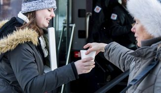 In this  Jan. 31, 2018, photo, Shirley Arendt, right, offers a hot beverage and snacks to students in Como, Minn. Every Wednesday morning, Arendt and other volunteers from Southeast Christian Church prepare and distribute coffee, hot chocolate and cookies to commuters and Como residents along 15th Avenue. (Carter Blochwitz/The Minnesota Daily via AP)
