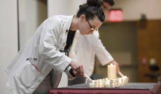 In a Jan. 31, 2018 photo, Brittany McCune lights a candle during a Cadaver Memorial Service, at Texas A&M's Health Professions Education Building in Bryan, Texas, as medical students from the Class of 2021 remember and honor 27 individuals who donated their bodies so students could learn from cadavers.   (Laura McKenzie/College Station Eagle via AP)