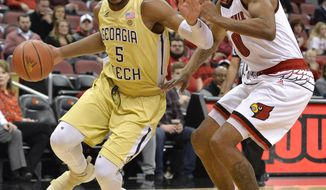Georgia Tech guard Josh Okogie (5) attempts to drive past Louisville forward V.J. King (0) during the first half of an NCAA college basketball game Thursday, Feb. 8, 2018, in Louisville, Ky. (AP Photo/Timothy D. Easley)