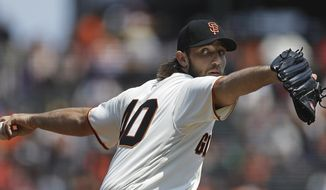 FILE - In this Aug. 20, 2017, file photo, San Francisco Giants pitcher Madison Bumgarner works against the Philadelphia Phillies during a baseball game in San Francisco. Giants manager Bruce Bochy's first glimpse at his new roster gives him hope the Giants will feature a lineup much like the ones of several years ago, when his club was capturing World Series championships every other year. (AP Photo/Ben Margot, File)