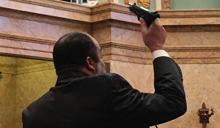 Mississippi state Rep. Charles Young holds up an unloaded pistol during a debate in the state House chamber on Thursday, Feb. 8, 2018. Young, a Democrat from Meridian, says he was making a point about the hypocrisy of laws and rules about where people may carry guns. He questioned a rule of the Mississippi House and Senate that says only law enforcement officers may have a firearm in the state Capitol; anyone else wanting to carry a gun in the Capitol must have permission of a majority of the House and Senate. Young displayed the gun a day after the Mississippi House passed a bill that would void rules limiting where people can carry guns on public property, including college campuses. (AP Photo / Emily Wagster Pettus)