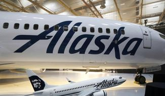 FILE - This Jan. 25, 2016, file photo,  the new logo of Alaska Airlines is shown next to a model of a plane with the old livery in Seattle. An Alaska Airlines flight to Seattle was forced to return to Anchorage, Alaska, early Wednesday, Feb. 7, 2018, after a passenger locked himself in the bathroom, took off all his clothes, and refused to follow crew instructions. (AP Photo/Ted S. Warren)
