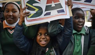 FILE - In this July 19 2012, file photo, young children join hundreds of fans gathered at Johannesburg's O.R. Thambo Airport to bid farewell to the South Africa Olympic team members who were departing for the games in London. The Olympics could be finally heading to Africa, but first there'll be a tiny step to take: hosting the much smaller Youth Olympic Games in 2022. (AP Photo/Emoke Bebiak, File)